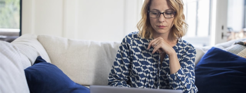 woman looking at her laptop   American Verified Home Inspection   protecting your digital house from cybercrime
