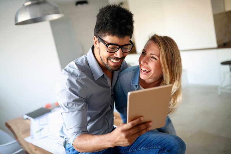 Couple laughing looking ipad